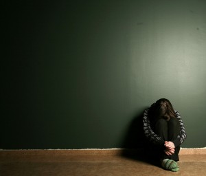 lone person curled against a green wall