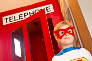 Superhero costumed kid in front of telephone booth