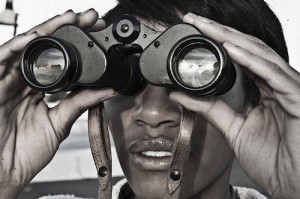 Close-up photo of person looking through binoculars.