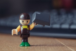 photo of computer keyboard's ctrl key held up by mini figure