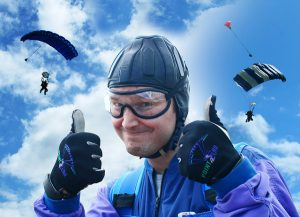 parachutist giving two thumbs up with parachuters landing in background