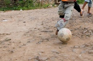 Photo of shoeless children playing soccer in the dirt  by Danumrthi Mahendra used under CC BY-2.0 license.
