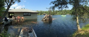 photo of people sitting on a flooded dock at the boat house