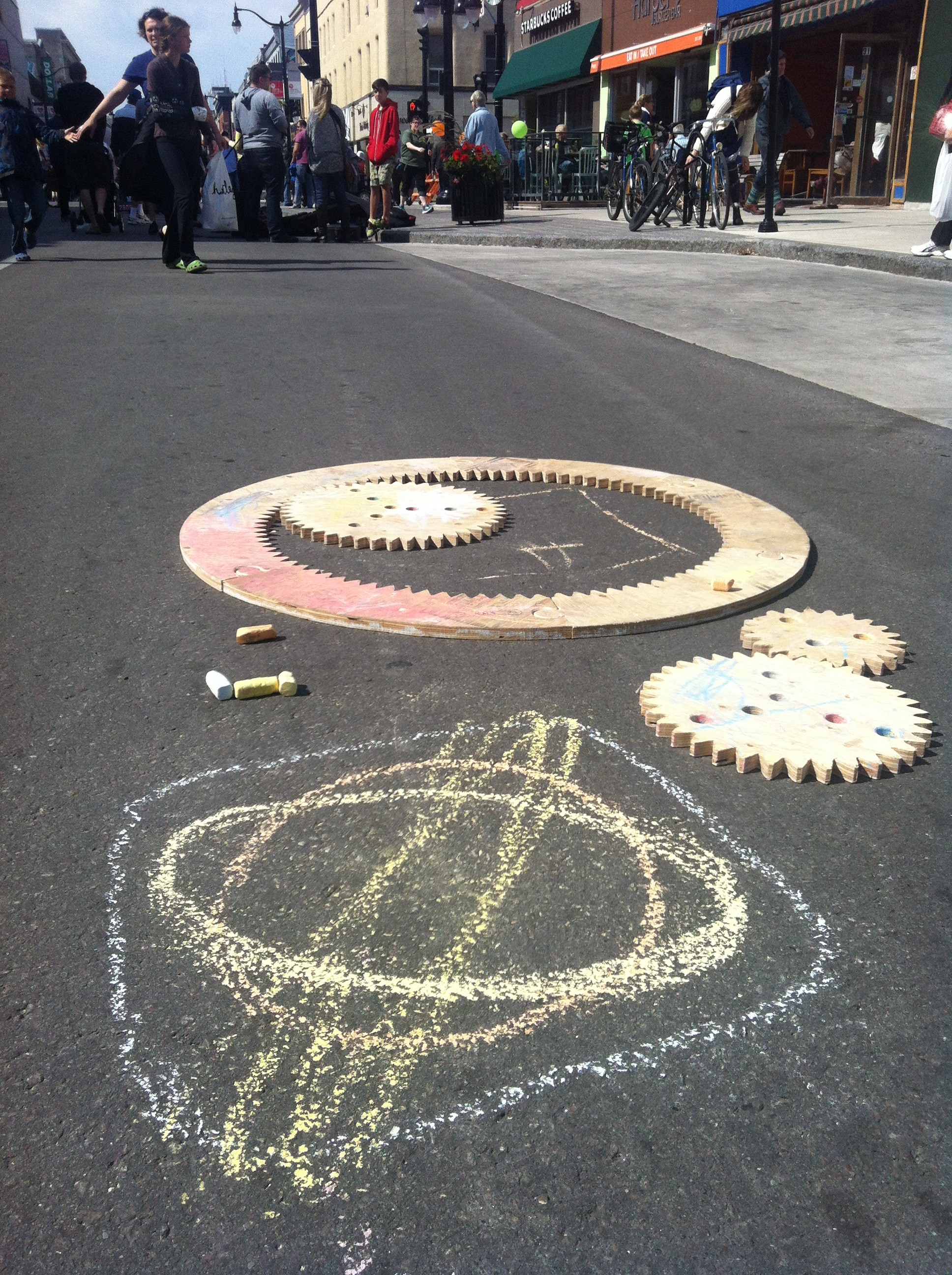 photo of sidewalk sized spirograph in action