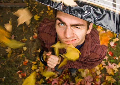 photo looking down on skeptical-looking man who has yellow leaves falling on him