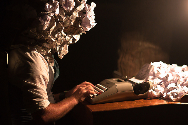 Photo of crumpled-paper-head writer with typewriter