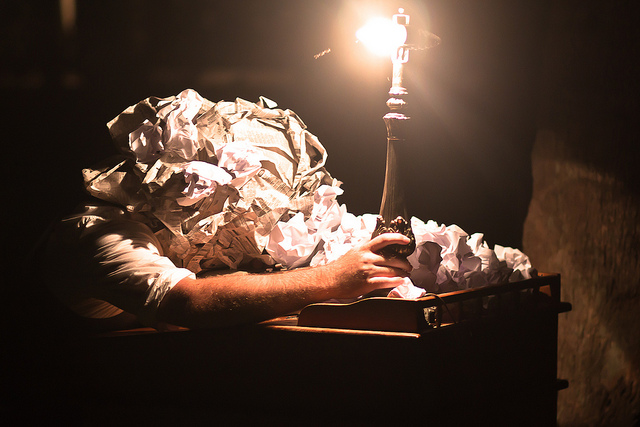 Photo of a head buried in crumpled paper lit by a bare lightbulb