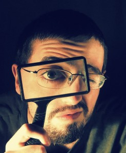 man with glasses peering through a rectangular magnifying glass