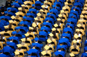 graduation hall with rows of blue & yellow caps and gowns