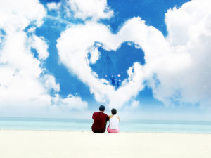 couple on beach beneath heart-shaped cloud