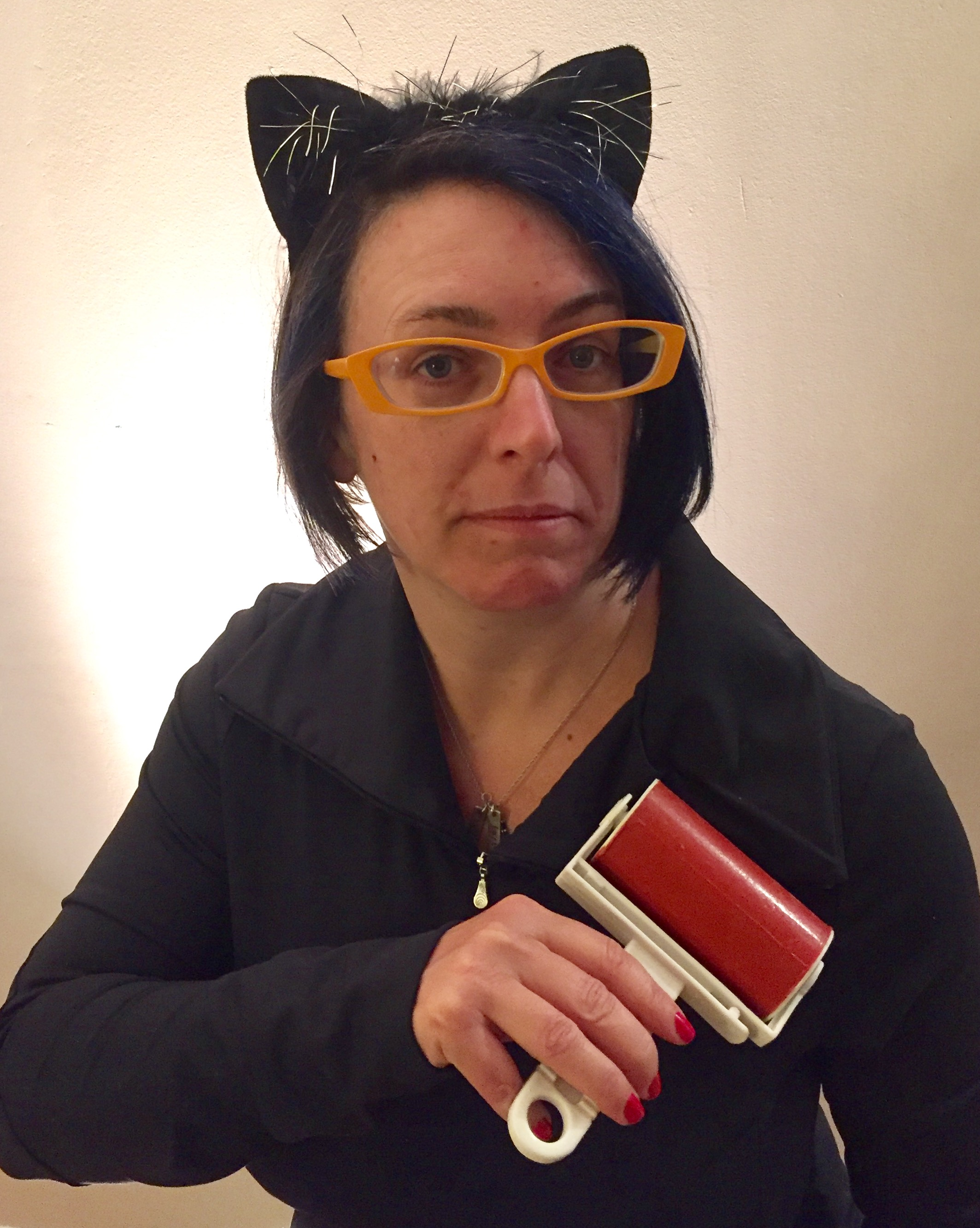 woman in cat ears using a lint roller, looking surprised