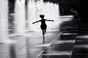 girl running through fountain