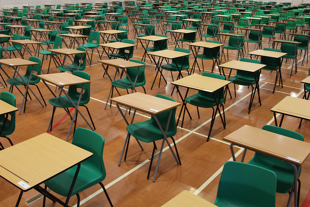 gym set up with rows of desks for exams